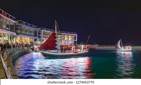 Manama, Bahrain - 15th December 2018: A traditional fishing Boat (Dhow) with Large Bahrain flag near Bahrain Water Garden, (Selective focus)