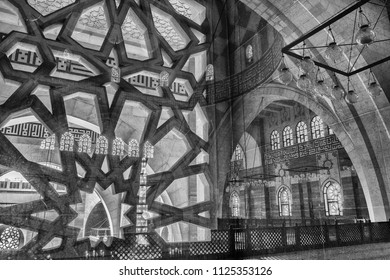 MANAMA, BAHRAIN - 20 DECEMBER, 2017: The interior arches and windows of the Grand Mosque reflected in the glass of an interior window with a stonework lattice looking out onto an internal courtyard.
