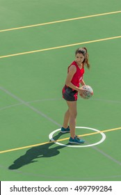 MANAMA, BAHRAIN - 4 MARCH, 2016: A young woman playing centre stands in the centre circle holding a netball and looks for her team mates to pass to at the start of a netball match.