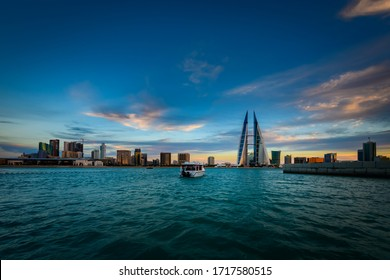 MANAMA, BAHRAIN - April 27, 2020: Beautiful view of iconic building Bahrain World Trade Center with skyline during sunset in seafront with tourist boat