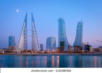 MANAMA, BAHRAIN - JULY 25, 2018: Double exposure view of iconic buildings Bahrain World Trade Center and Bahrain Financial Harbour with moon background after sunset Manama, Bahrain