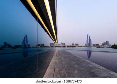 MANAMA, BAHRAIN - MAY 2019 : Bahrain World Trade Center with beautiful mirror reflection at sunset, WTC is one of the iconic building in Bahrain with wind turbines.