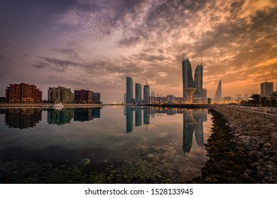 Manama, Bahrain - OCTOBER 04, 2019: Beautiful sky and Manama skyline with clouds and reflection during sunrise