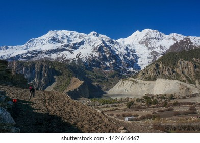 Manang, Nepal - April 24, 2019: Unidentified female farmer is seen working with a snowy mountain view