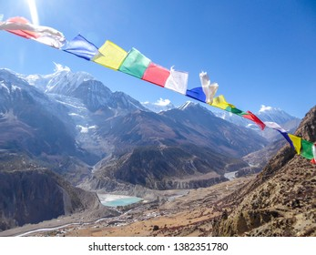 "Manang/Nepal - 10 30 2018: Waving flags with mantra ""Om mani padme hum"" on them. Wind blows them over Himalayan peaks. Very weary flags. High peaks covered with snow. meditation and retreat"