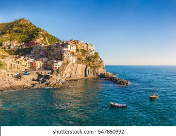 Manarola, Cinque Terre, Italy before sunset with boats floating
