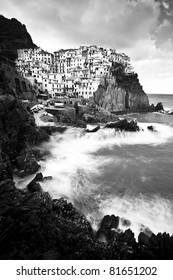 Manarola fisherman village in a dramatic windy weather. Manarola is one of five famous colorful villages of Cinque Terre in Italy, suspended between sea and land on sheer cliffs upon the wild waves.