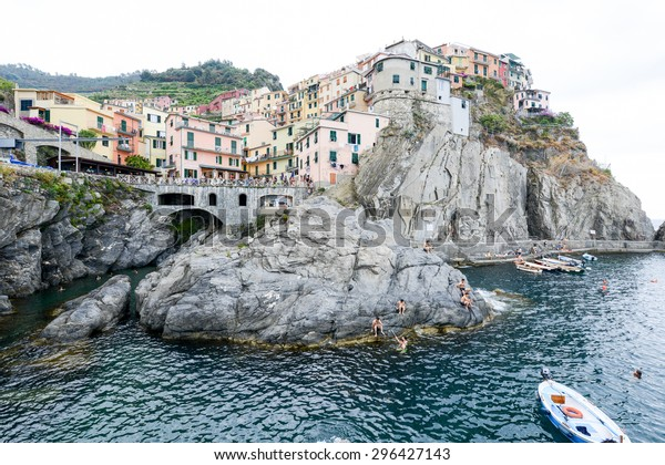 Manarola, Italy - 8 July 2015: people swimming and sunbathing  at the port of the village of Manarola on Cinque Terre, Italy