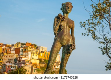 MANAROLA ITALY - APRIL 25; Woman with Grape bronze statue was created by Antonio Pujia in 1971 against background traditional hillside village buildings Cinque Terre April 25 2011, Manarola Italy