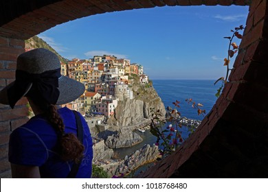MANAROLA, ITALY, June 2, 2017 : A young woman with a hat admires the view on the old village of Manarola in Cinque Terre National Park.