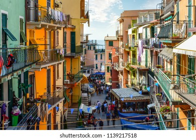 Manarola, Italy - September 25 2017: Tourists walk the main street past cafes and shops on their way to the sea in the Cinque Terre village of Manarola, Italy