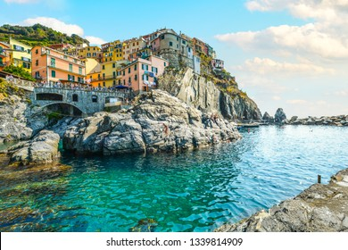 Manarola, Italy - September 27, 2018: Tourists enjoy the Ligurian sea on a sunny day in early autumn at the resort village or Manarola, Italy, part of the Cinque Terre, an Unesco World Heritage Site