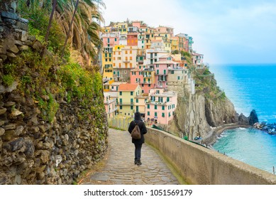 Manarola, Liguria, Italy - December 2017: Woman walking on a path with view on the small traditional Italian village of Manarola  a popular tourist destination in Cinque terre, Liguria, Italy