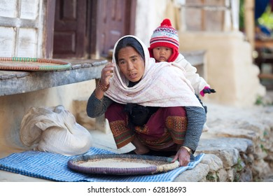 MANASLU AREA, NEPAL - DECEMBER 06: Peasant woman in national clothes with baby from gorkhas village on December 06, 2009 in Gorkha District, Nepal