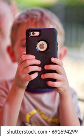 Manassas, Virginia, USA - June 2, 2017: A young boy plays on his parent's iPhone 6 while waiting for his lunch to arrive at a local restaurant.