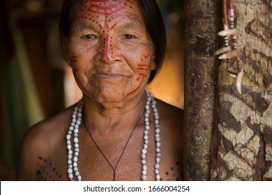 Manaus, Amazonas, Brazil - August 17, 2016:  Senior indigenous woman with traditional adornments and tribal facial paint in a hut entrance at Dessana Village, near Manaus, in the Brazilian Amazon