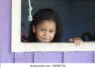 MANAUS, BRAZIL, MARCH 25: Portrait of Indian Brazilian young girl shirtless and smiling while looking at the camera standing by the window. Brazil 2015