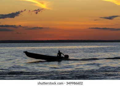 MANAUS, BRAZIL, MARCH 26: Sunset and silhouette of a man sitting on a small wooden boat and cruising on the Amazon River, Brazil 2015