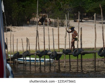 Manaus/Amazonas/Brazil - November 16, 2015: Indigenous man of the Tukano-Dessana ethnic group walking on pier on the Rio Negro, with boat and indigenous village in the background