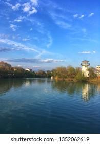Manavgat, Antalya / Turkey - March 21, 2019: A river Manavgat seen through green trees, blue sky, clouds. Manavgat river in Antalya. Blue river landscape from Manavgat, Antalya, Turkey.