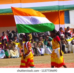 Manbazar, West Bengal / India - 26th January 2018 : Indian under privileged tribal school girls holding and waving national flag and performing dance at republic day parade and celebration