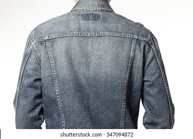 A man(boy, male) wearing blue denim jacket back side close up isolated white at the studio.