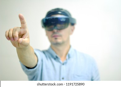 A man-businessman with a virtual reality headset controls his hand. Future technology.