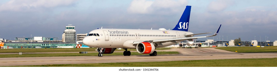 Manchester Airport, England, 23rd October 2019, Scandinavian Airlines SAS, passenger aircraft, EI-SIA an Airbus A320 ready for take-off with the airport terminal and buildings in the background.