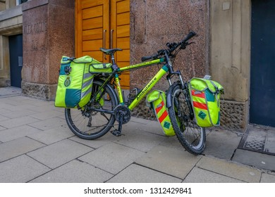 Manchester central, England, UK - January 20, 2019: NHS Cycle response unit, Ambulance parked on the pavement.  Bicycle is loaded with pannier bags of equipment.