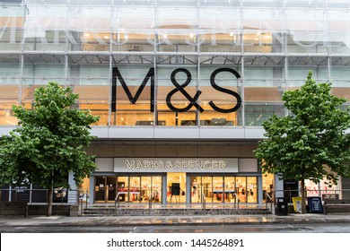 Manchester City Centre, Manchester/UK - July 6 2019: Marks & Spencer store front on Market Street in Manchester City Centre. No people in shot. Trees either side with glass front M&S logos