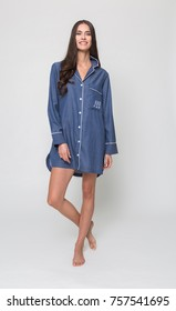 manchester, England, 05/07/2016, A beautiful tall brunette girl in a blue short night pyjama dress, night wear, evening sleep wear. isolated on a white backdrop.