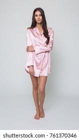 manchester, England, 05/07/2016, A beautiful tall brunette girl in a silky pink pyjama dress, night wear, evening sleep wear.