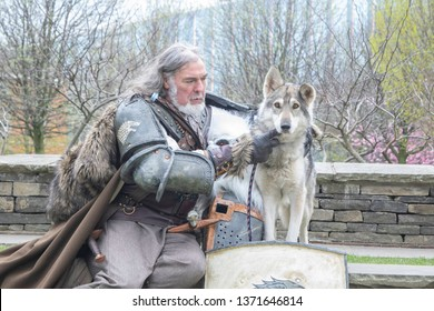 MANCHESTER, ENGLAND - APRIL 14, 2019: Ned Stark Cosplayer poses with Dog at the Manchester Anime and Gaming Convention