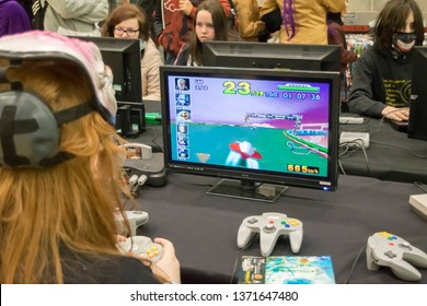 MANCHESTER, ENGLAND - APRIL 14, 2019: Attendee playing F Zero X on the Nintendo 64 at the Manchester Anime and Gaming Convention