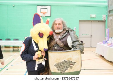 MANCHESTER, ENGLAND - APRIL 14, 2019: Ned Stark Cosplayer poses with unidentified cosplayer at the Manchester Anime and Gaming Convention