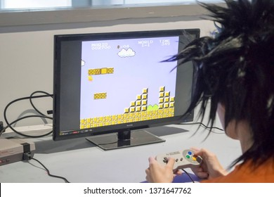 MANCHESTER, ENGLAND - APRIL 14, 2019: Goku cosplayer playing Super Mario on the Super Nintendo Entertainment System at the Manchester Anime and Gaming Convention