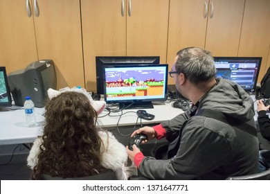 MANCHESTER, ENGLAND - APRIL 14, 2019: Attendee playing Sonic the Hedgehog on the Sega Master System at the Manchester Anime and Gaming Convention