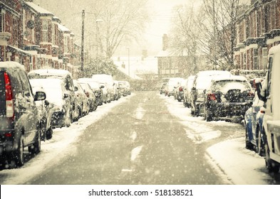 Manchester, England. Cars cover, houses of snow on street. The winter storm, causing flight delays and traffic problems.