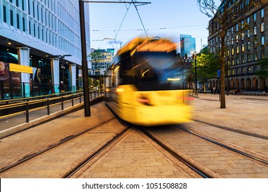 Manchester, England. Light rail yellow tram in the city center of Manchester, UK in the evening. Motion blurred tram with modern buildings