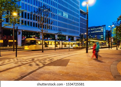 Manchester, England. Light rail yellow tram in the city center of Manchester, UK in the night. Motion blurred tram with modern buildings