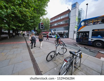 Manchester, England, UK - 10/09/2019: All Saints/Manchester (UK), a Manchester Metropolitan University building main road crossing of Oxford road, showing traffic, cyclist, cycle lane and cycle stand.