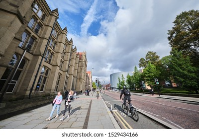 Manchester, England, UK - 10/09/2019: Manchester University building (left) with a cyclist in cycle lane on Oxford road into Manchester (UK).