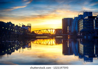 Manchester, England / United Kingdom - 21 February 2019:  Manchester Ship Canal in Salford and Trafford. View to bridge of MediaCityUK downtown buildings and facilities in evening.