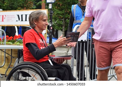 Manchester. Greater Manchester, UK. July 14, 2019. Volunteer in wheel chair at Manchester International Festival give out brochures in Festival Square. Banner and security guard visible in background