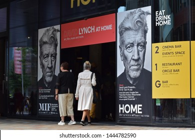 Manchester, Greater Manchester, UK. July 7, 2019. Entrance to Home performing arts theatre with posters for the David Lynch exhibition My Head is Disconnected. Two women enter the theatre.