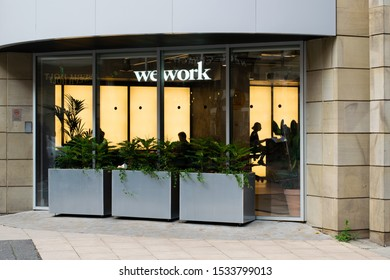 Manchester Greater Manchester UK October 17 2019 WeWork offices in Dalton Place John Dalton Street with sign and view through window and people working in front of illuminated panels