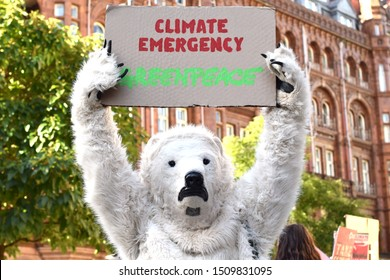 Manchester Greater Manchester UK September 20 2019 Youth Strike for Climate at St Peter's Square Man in polar bear costume holds placard above his head with text Climate Emergency Greenpeace