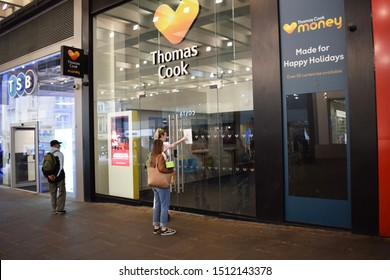Manchester Greater Manchester UK September 23 2019 Thomas Cook store Market Street permanently closed and in darkness.  Two women read an A4 printed sign stuck to the window referencing the CAA