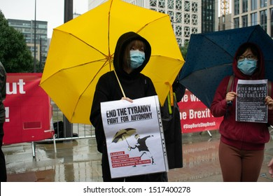 Manchester Greater Manchester UK September 29 2019 Protester outside the library with yellow umbrella and face mask holds a sign with text End the Tyranny Fight for Autonomy
