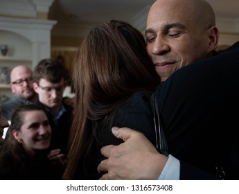 Manchester, N.H./USA - Feb. 17, 2019: U.S. Sen. Corey Booker, D-N.J., hugs a woman at a house party during his first trip to New Hampshire as a presidential candidate.